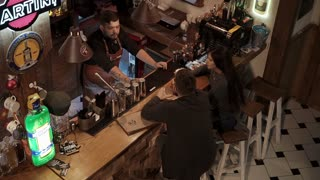 Rosa Khutor, RUSSIA - FEB, 2018: friends are drinking in bar and talking with handsome barman. Top view on bar rack and people, signs with inscriptions of brand