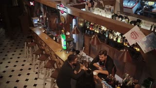 Rosa Khutor, RUSSIA - FEB, 2018: pair of visitors in a bar in deep night time are sitting near bar counter. They are chatting with lonely barman, view from top