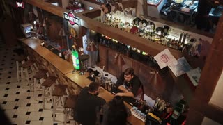 Rosa Khutor, RUSSIA - FEB, 2018: top view on hall of night club with bar rack. Couple is drinking cocktails and barman is speaking with them