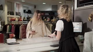 Russia Togliatti - December 2017 : a young and pretty woman made a purchase in a boutique, a lady pays for an acquisition using a smartphone, the cashier serves her terminal
