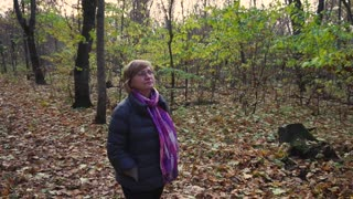 Senior woman spends her free time walking through an autumn forest.