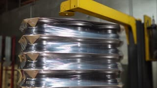 Several layers of rims wrapped up on the machine. Ready to go on pallets.