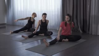 Several women in the yoga center perform stretching the body with asanas. The women lean toward the leg, stretching the back of the thigh.