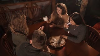 Shot from above of four adult people having a great time in a cafe. They are talking and very to see each other.