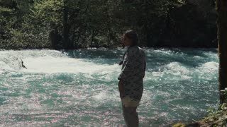 Shot from behind of a brunette woman spending day by the flowing river in the forest. Beautiful day on the nature. Fast stream.