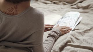 Shot from behind of brunette woman reading journal lying in bed. Back decorated with henna traceries. Relaxing in bed.