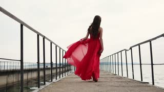 Shot from behind of charming woman walking along the bridge on the shore. She is dressed very beautiful.