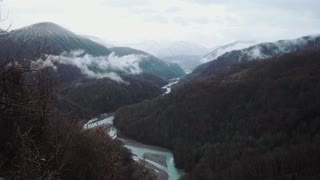 Shot from the top of the mouintain on the dark and foggy forest. Beautiful flowing river separates forest.