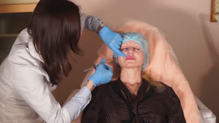 Shot of the process of introducing fillers into the cheek zone of a middle-aged woman's face. The cosmetologist introduces the injection implant under the skin.