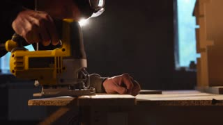 Side view shot of a professional carpenter using electric saw to deal with a wood boards. He is going along the drawn line.