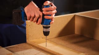 Skilled handy man is using electric drill to make holes at the bottom of wood board. He is using thin drill.