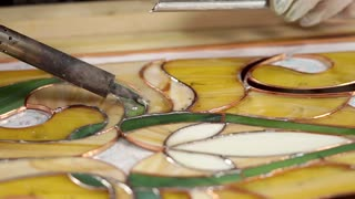 Skilled workman is covering frame of stained-glass by tin solder. Expensive technology of producing using copper tape and manual labour