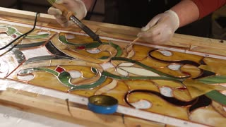 Skilled workman is processing copper tape of stained-glass panel. He is using tin solder and soldering iron, assembling and fixing beautiful hand made stained-glass
