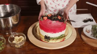Skillful pastry chef is demonstrating her finished cake. It decorated with strawberries, blueberries and glaze.