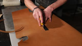 Skinner is cutting out a detail of bag from treated animals skin. There are many tools on his table, master is working on an exclusive leather accessories.
