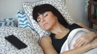 Sleepy woman is lying in bed after waking up with alarm clock. She is looking at the time on the phone and stretching.