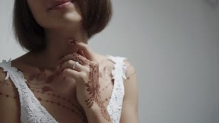 Slim fragile girl with body art in mehndi style on hands. She is standing in white background and holding hand near neck