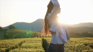 Slim girl is stretching hands up and enjoying sunny summer evening. She is standing in background of amazing tea plantations and mountains