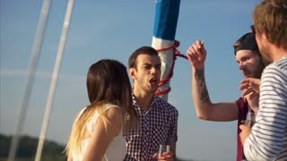 Slow motion shot of a cheerful friends enjoying party on the yacht. They dancing and singing with drinks