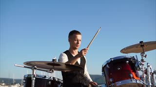 Slow motion shot of a drummer performing during music band concert in the harbour