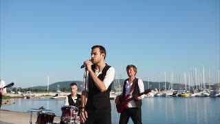 Slow motion shot of a music boy band giving performance in the harbor