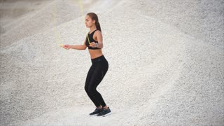 Slow motion shot of a young athletic woman skipping rope during the training on the hills of gravel pit. Doing sports alone outside the city