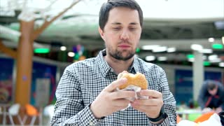 Slow motion shot of a young man eating hamburger in food court of shopping centre. Quick but unhealthy way to have a snack.