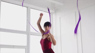 Slow motion shot of beautiful young woman dancing with ribbon. Rhythmic gymnastics performance