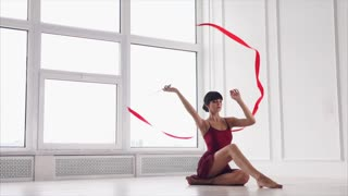 Slow motion shot of graceful woman dancing with ribbon in the studio. She doing elements sitting on the floor