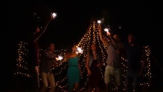 Slow motion shot of happy friends enjoying night beach party and dancing with sparklers in the darkness