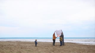 Slow motion shot of parents and two kids on the beach launching heart-shaped paper lantern. Family fun outdoor