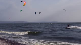 Slow motion shot of people kitesurfing near the shore. Extreme water sports