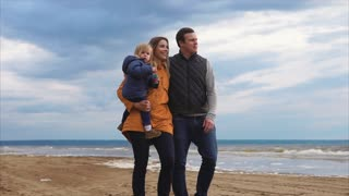 Slow motion steadicam shot of a family couple and their little daughter having a walk along the sea. Man and woman talking and enjoying fresh chilly weather