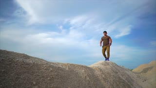 Slow motion steadicam shot of a young athletic man running on the top of gravel hills. Working out at industrial mining area