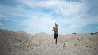 Slow motion steadicam shot of a young woman running among the hills. Jog training at one with nature. Healthy lifestyle