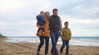 Slow motion steadicam shot of close-knit family having a walk at the beach on a cold day. Happy mother, father, son and little daughter enjoying time together