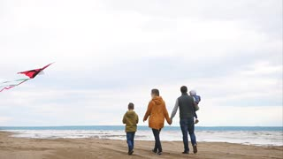 Slow motion steadicam shot of parents with two children walking along the sea on chilly day. Father carrying baby and holding womans hand, elder son flying a kite