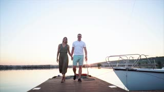 Slow motion steadicam shot of young man and woman holding hands and walking along the pier in the harbour at sunset. Romantic moments