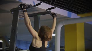 Slow shot at a woman who performs the correct technique of lifting the body on the simulator, for pumping the spinal complex, the woman is in the gym.