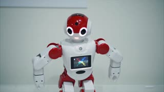 Small red and white robot dancing and blinking. Concept of robotic toys and games. Robot with screen.