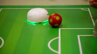 Small round robot playing football on the table. Concept of electronic robot toys and games.
