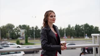 Smiling girl in leather jacket having coffee break outside. Young woman with wistful look holding a cup of hot drink in hands. City scene
