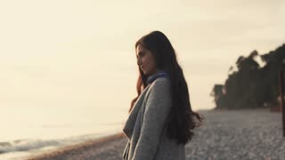 Smiling young woman is relaxing on beach in autumn evening during sunset. She is turning to camera, looking and laughing