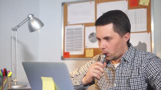 Smoking electric cigarettes at workplace in office. Man in casual wear working at notebook.