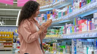 SOCHI, RUSSIA - DECEMBER 15, 2020: Young pretty brunette loves visiting beauty care stores and buy different products for herself. She wants to buy cleansing foam