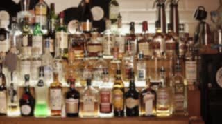 Spirit drinks in bottles in a bar of night club. Camera is showing an assortment of alcoholic beverages