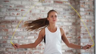 Sports woman is skipping rope indoor. Intense work-out of young pretty female athlete before training in gymnasium.