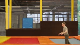 Sportsman is jumping from one bouncer to other in a training hall. Funny sport entertainment for young and active people