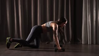 Sportswoman is doing full press ups exercise, using kettlebells. She is standing in a prone position by raising and lowering the body using the arms.