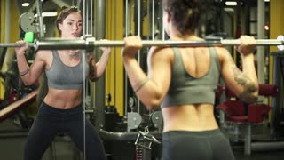 Sporty brunette is holding a rod on shoulders and crouching in training hall. She is looking at herself on a large mirror, work-out for keeping herself in good shape